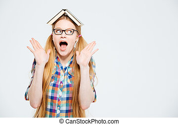 Amazed female student with book on head standing isolated on...