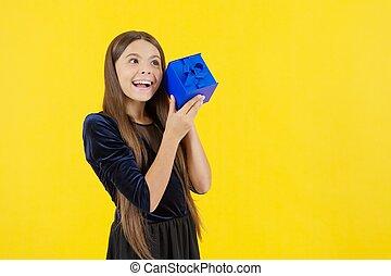 amazed girl kid shopper with happy face holding gift box, copy space, shopaholic
