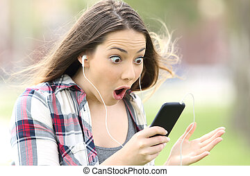 Amazed girl listening on line music and watching media...