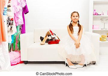 Amazed girl sitting on white sofa with shoes near