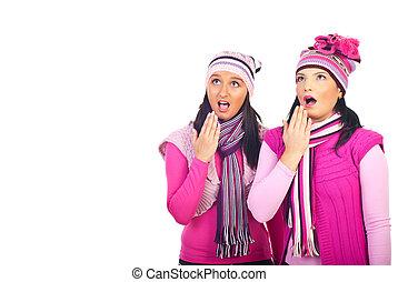 Amazed girls in pink woolen clothes