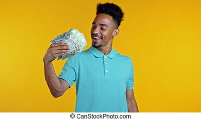 Amazed happy excited african man with money - U.S. currency dollars banknotes on yellow studio wall. Symbol of success, gain, victory