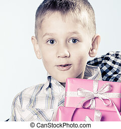 Amazed little boy with gift boxes