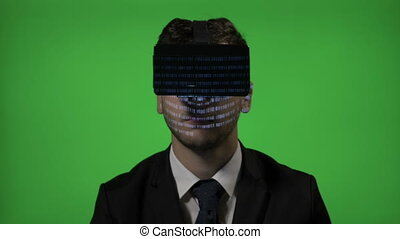 Amazed man business manager experiencing VR virtual reality goggle glasses reading computer programming code on green screen
