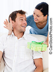 Amazed man receiving a present from his girlfriend