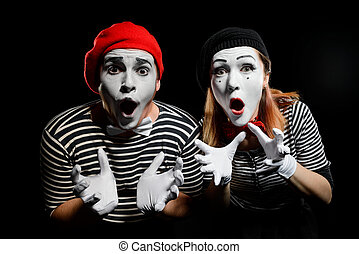 Amazed mimes with dropped jaws on black background