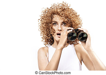 Amazed redhead girl looking throug the binoculars