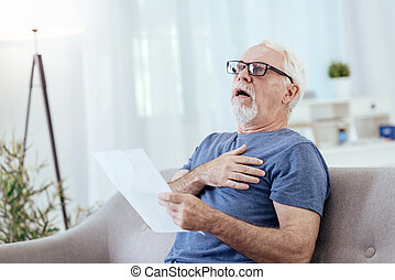 Unexpected heart attack. Speechless senior man opening mouth and touching chest