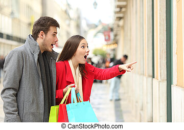 Amazed shoppers finding sales in a storefront