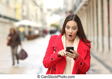 Amazed woman checking smart phone in the street