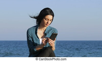 Amazed woman finding offers on phone on the beach - Amazed...