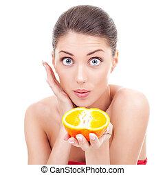 amazed woman holding an orange