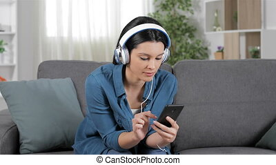 Amazed woman listening to music on a sofa - Amazed woman...