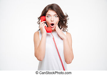 Amazed woman talking on the phone tube