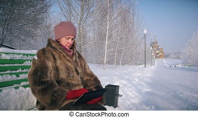 Amazed wow woman looking a tablet application in a snowy...