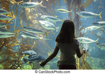 Amazed Young Girl Standing Up Against Large Aquarium Observation Glass.