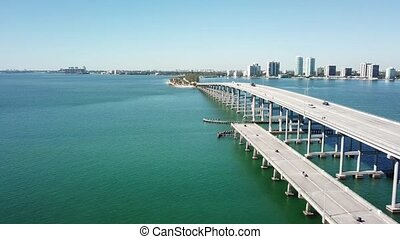 Amazing 4k aerial drone panorama shot of highway road on huge steel modern bridge across turquoise blue ocean cityscape