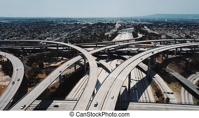 Amazing aerial panning shot of famous Judge Pregerson highway road junction with multiple complex flyovers and bridges. Cinematic background opening shot of iconic transportation masterpiece in USA.