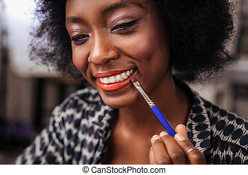 Amazing african american woman with curly hair smiling happily