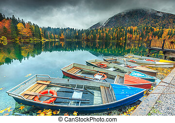 Amazing autumn landscape and colorful boats, Lake Fusine,...