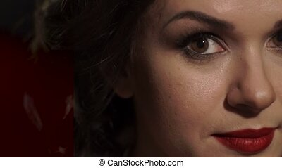 Amazing beautiful woman with red lips raises his head, opens brown eyes looking at the camera.