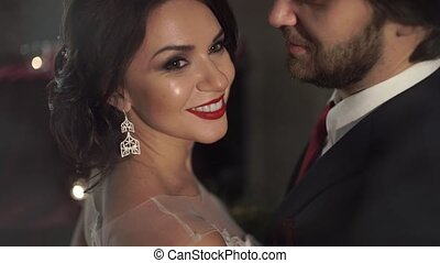 Amazing beautiful woman with red lips smiling broadly, as her husband hugs her gently