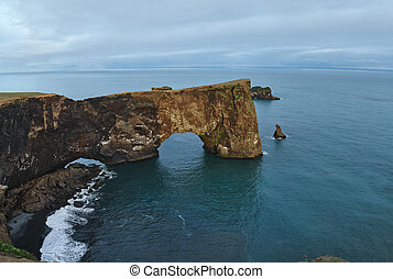 Amazing black arch of lava standing in the sea on small peninsula.