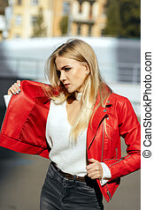 Amazing blonde model with long hair wearing red leather jacket posing in sun light