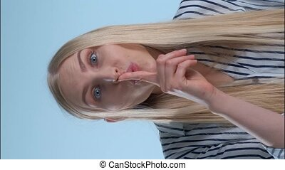 Amazing blonde woman making silence gesture on blue ...
