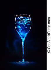 Amazing blue cocktail with ice cubes in high glass. Blue...