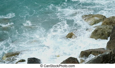 Amazing blue water with wave. Sea washes the stones in sunny...