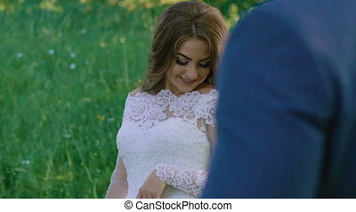 Amazing bride posing at her handsome groom, walking and kissing. Slowly