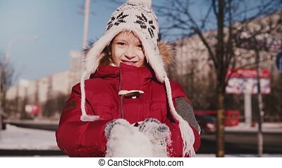 Amazing close-up portrait of fun cute little girl in warm winter clothes throwing snow in the air smiling slow motion.