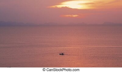 Amazing colors of tropical sunset. Sail boats floating on ocean horizon