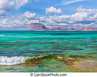 Amazing crystal clear blue water on a paradise beach - small wave - rocky island in the background