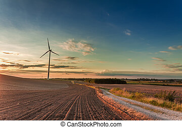 Amazing dusk at field with wind turbine in autumn