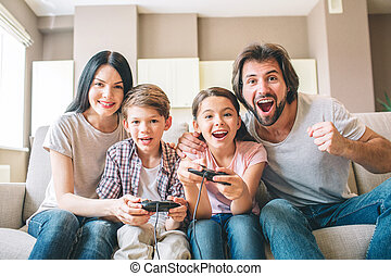Amazing family sits on sofa. Children are playing on video game. The game is intense. Guy rejoys. Girl is smiling as well. Mother helps to play her son.