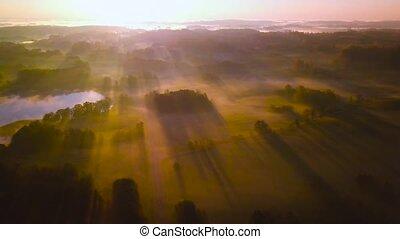 Amazing foggy scene of light rays above fields in Autumn