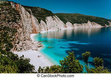 Amazing Fteri beach lagoon, Kefalonia, Greece. Tourists under umbrella chill relax near clear blue emerald turquoise sea water