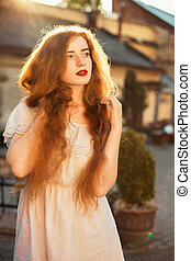 Amazing ginger girl with naked long wavy hair posing in sun glare at sunset