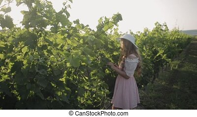 Amazing girl with long hair in the hat touches the leaves of the grapes