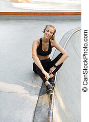 Amazing happy young sports woman sitting outdoors listening music.