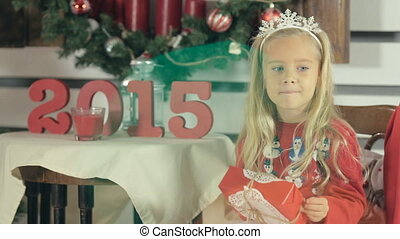 Amazing little girl with blue eyes and long white hair sits near a Christmas tree with box-gift and smiling