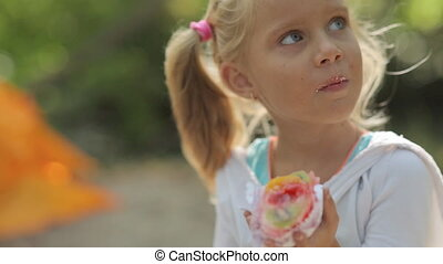 Amazing little girl with blue eyes eating cake with fruit on the nature