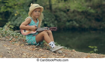 Amazing little girl with straw hat sitting by the river and playing on a little guitar