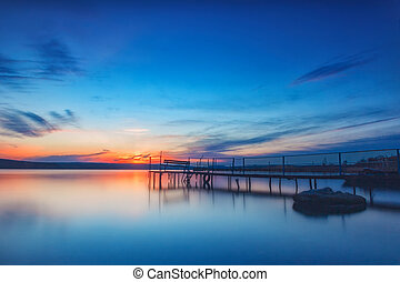 Amazing long exposure sunset on the lake with a bench on the wooden pier.