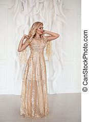 Amazing luxury elegant woman in stylish golden party dress posing before white feathers wall. Fashion beautiful sensual female with makeup, curly hair style in long prom gown.
