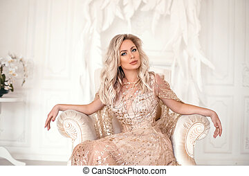 Amazing luxury elegant woman in stylish golden party dress sitting on modern armchair before white feathers wall. Fashion beautiful sensual female with makeup, curly hair style in long prom gown.