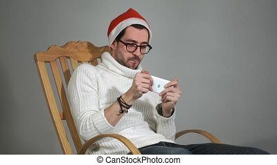 Amazing man in glasses and a red cap of Santa Claus playing a game on your phone