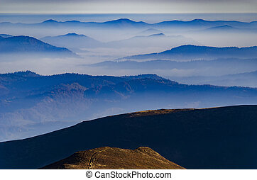 Amazing morning mountain landscape with blue mountain silhouettes